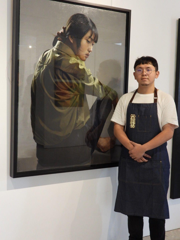 梁智翔與展出作品「眸」,專注主角眼神描繪。記者周宗禎/攝影