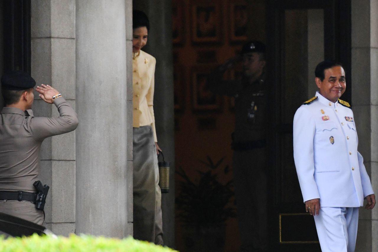 泰國總理帕拉育(右)廿五日與夫人離開總理府。 (法新社)