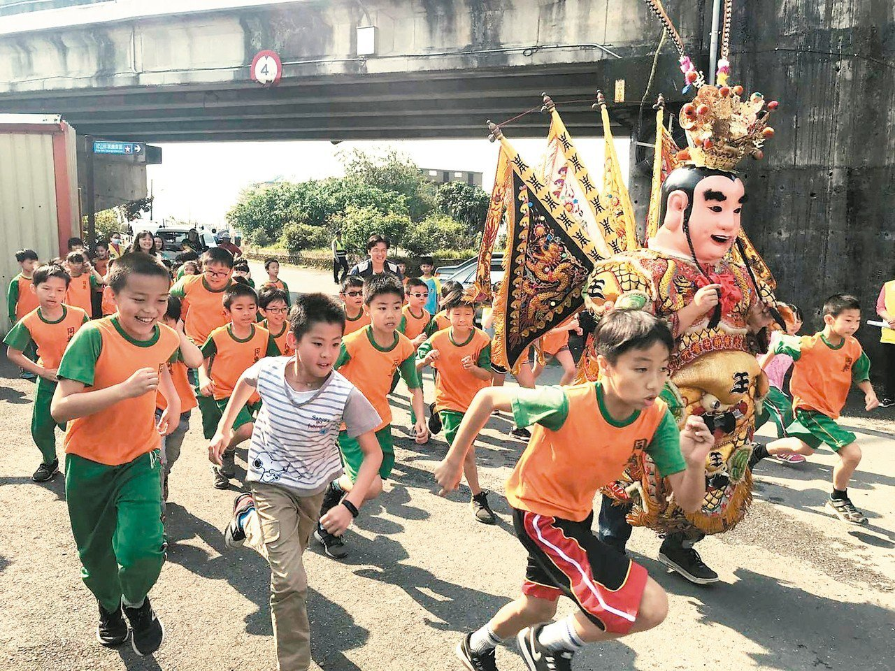 宜蘭同樂國小為慶祝兒童節舉辦路跑活動,學生與三太子一起跑,場面十分有趣。 圖/同...
