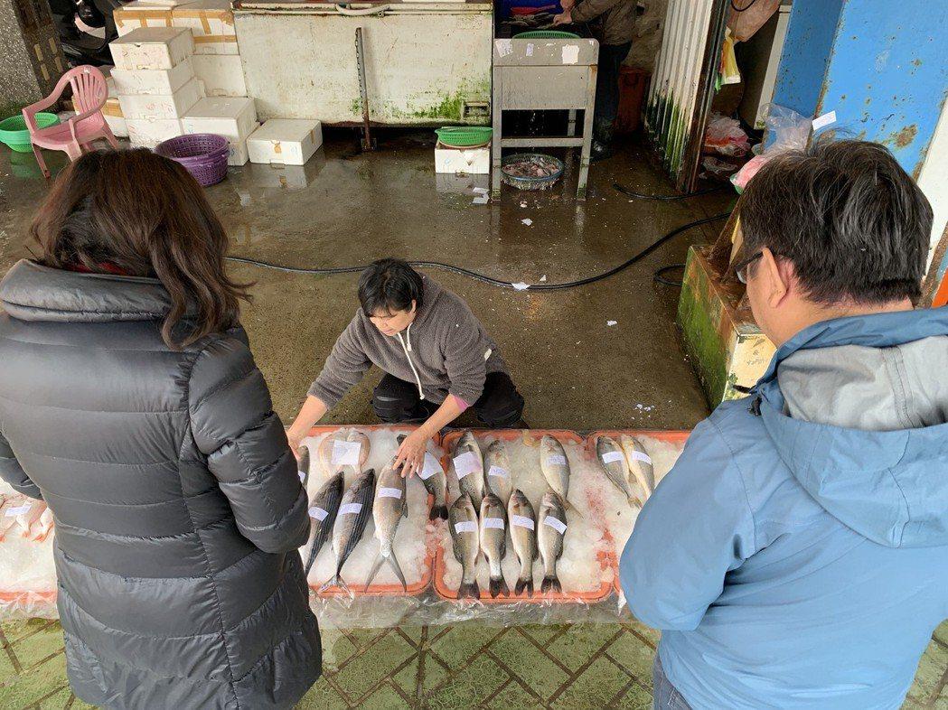 顧客拎鐵桶買魚,魚販挺開心的,「這樣我們也可以省點塑膠袋成本。」 記者黃昭勇/攝...
