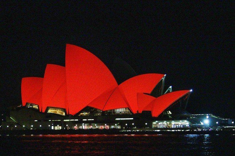 澳洲對中的官方政策,從80-90年代「澳洲的未來在亞洲」,其後逐漸形成「中國主宰我們的命運」。圖為2015農曆年,世界熟知的雪梨歌劇院屋頂披上中國紅。 圖/中新社