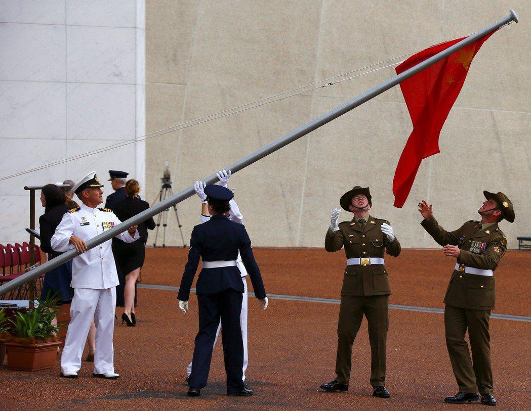 澳洲內部對國家是否應該調整對中關係,積極「向中靠」,有極多論戰。圖為2017年坎培拉國會歡迎中國總理李克強的官方儀式開始前,陸軍軍官調整一幅捲曲的中國國旗。 圖/路透社