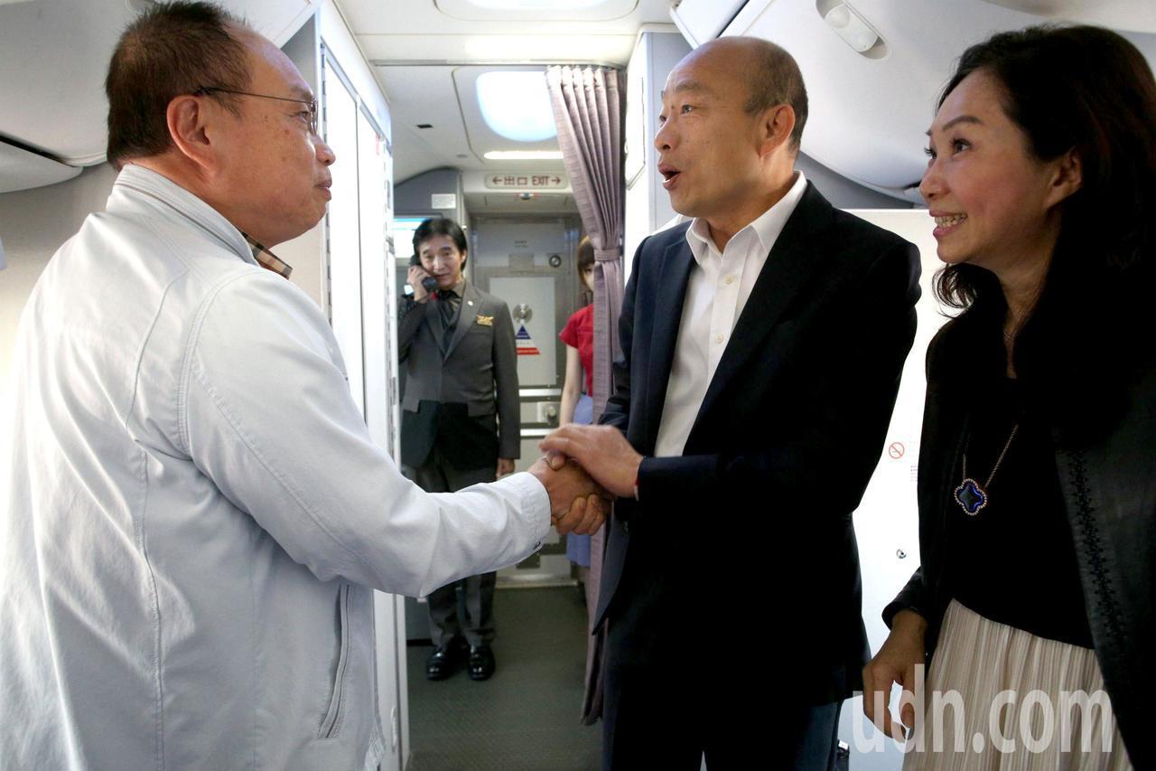 高雄市長韓國瑜(中)與夫人李佳芬(右)結束七天訪問行程,搭機返回高雄,上機後向同...