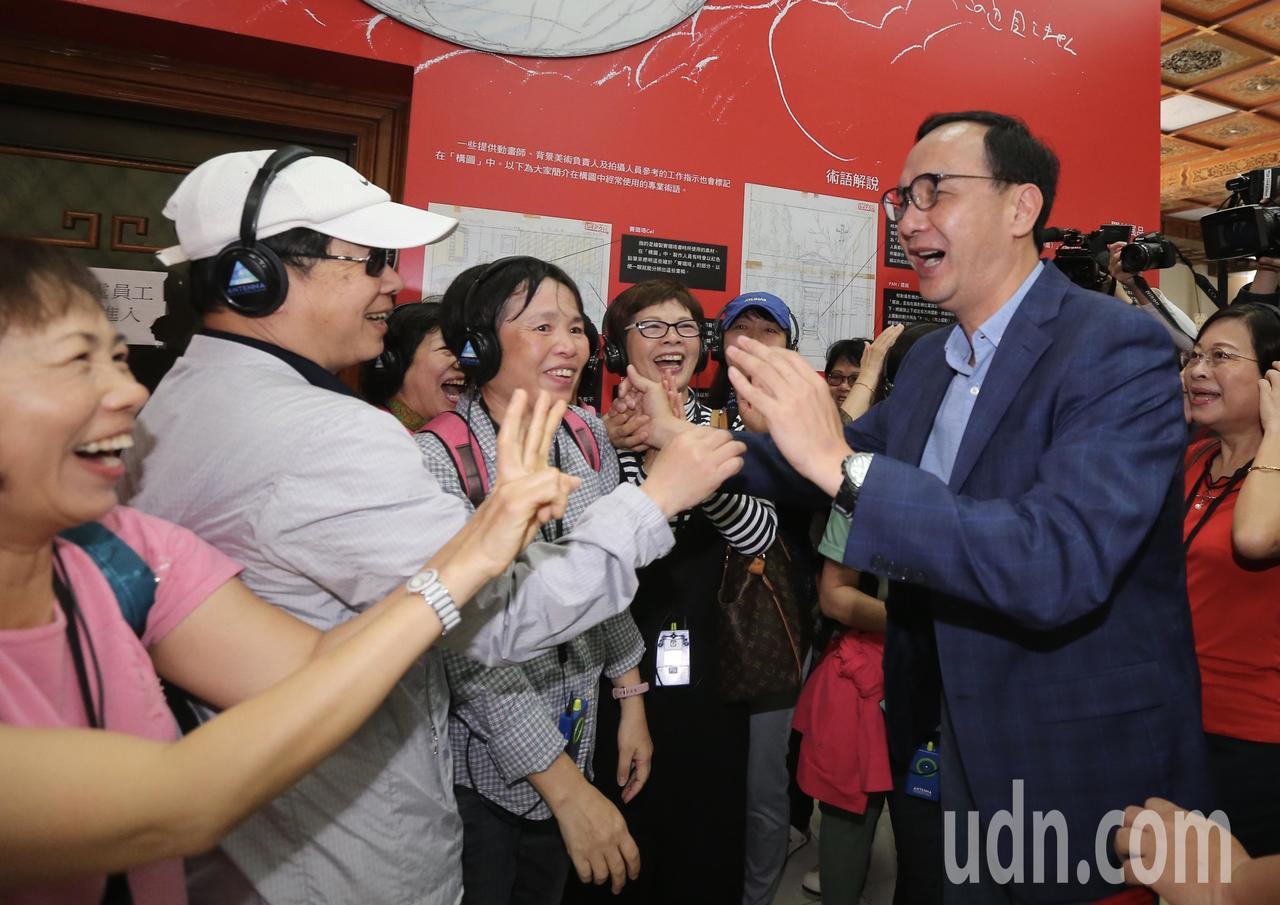 新北市前市長朱立倫(右)上午參觀吉卜力動畫手稿展,遇上一群熱情的民眾,他一一握手...