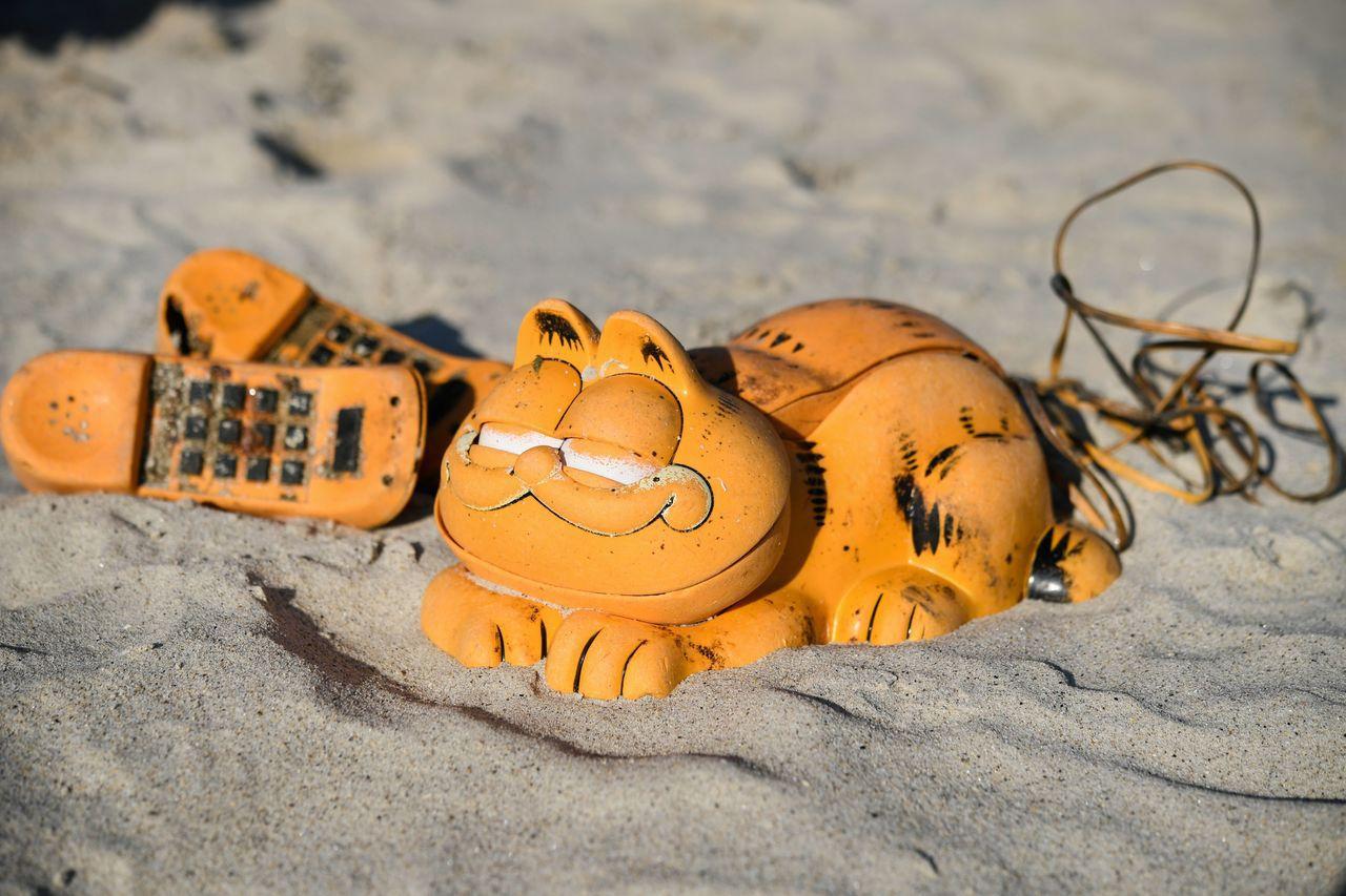 亮橘色「加菲貓」造型的電話機30多年來一直沖到法國一處海灘。 法新社