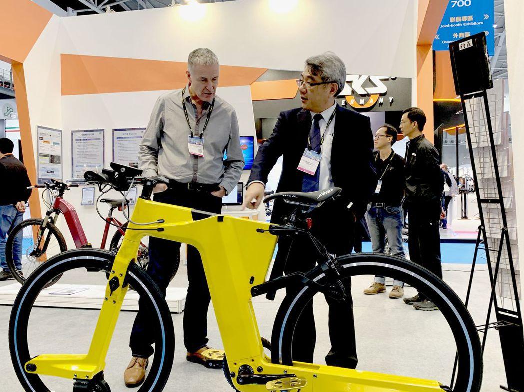 自行車中心總經理梁志鴻(右)向參觀者解說碳纖維板殼車架與無花鼓輪組設計成果。 C...