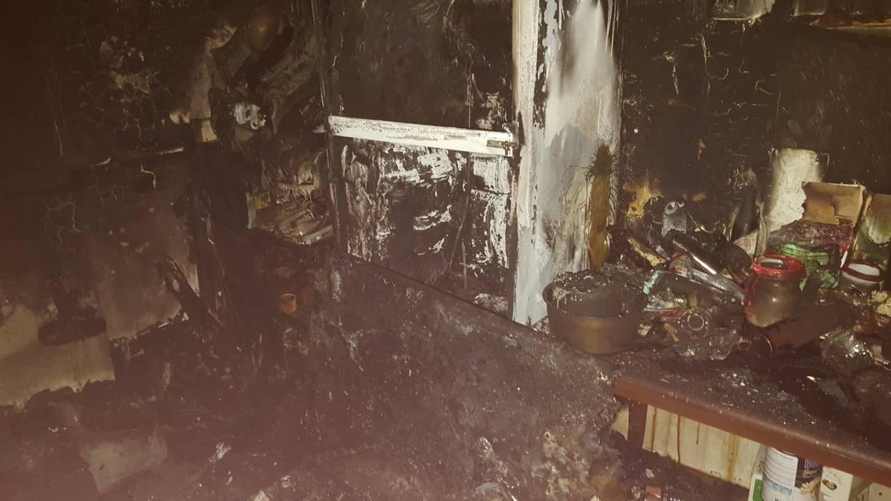 消防人員發現屋內廚房角落雜物起火,現場一片焦黑。記者邵心杰/翻攝
