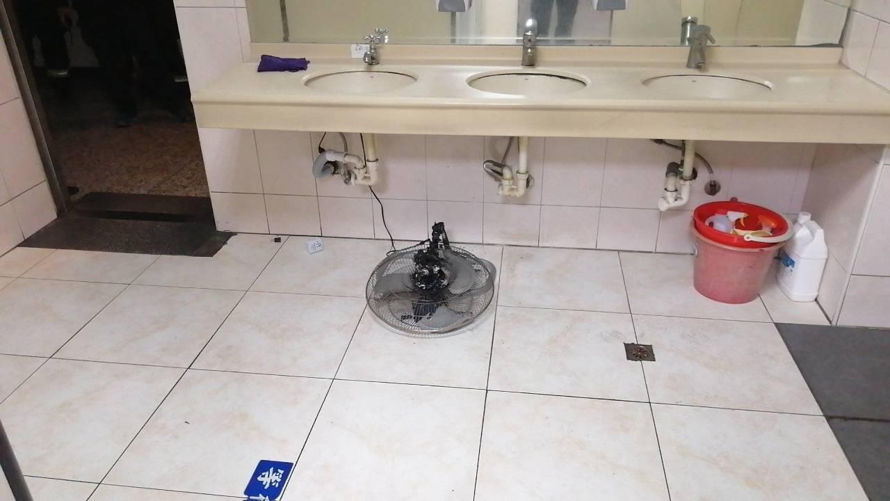 高雄市政府今天凌晨傳火警,消防隊員在男廁找到疑短路起火自燃的電風扇。記者林保光/...