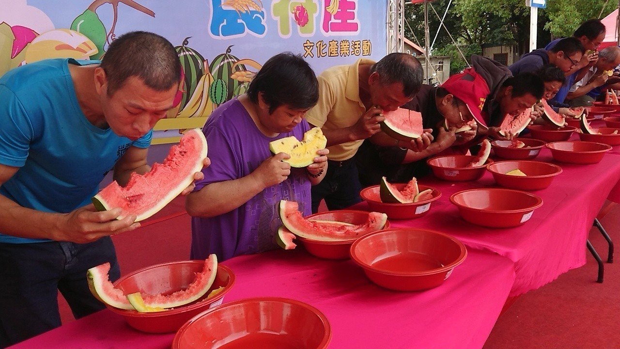 參加西瓜大胃王民眾, 大口快速吃西瓜。記者卜敏正/攝影