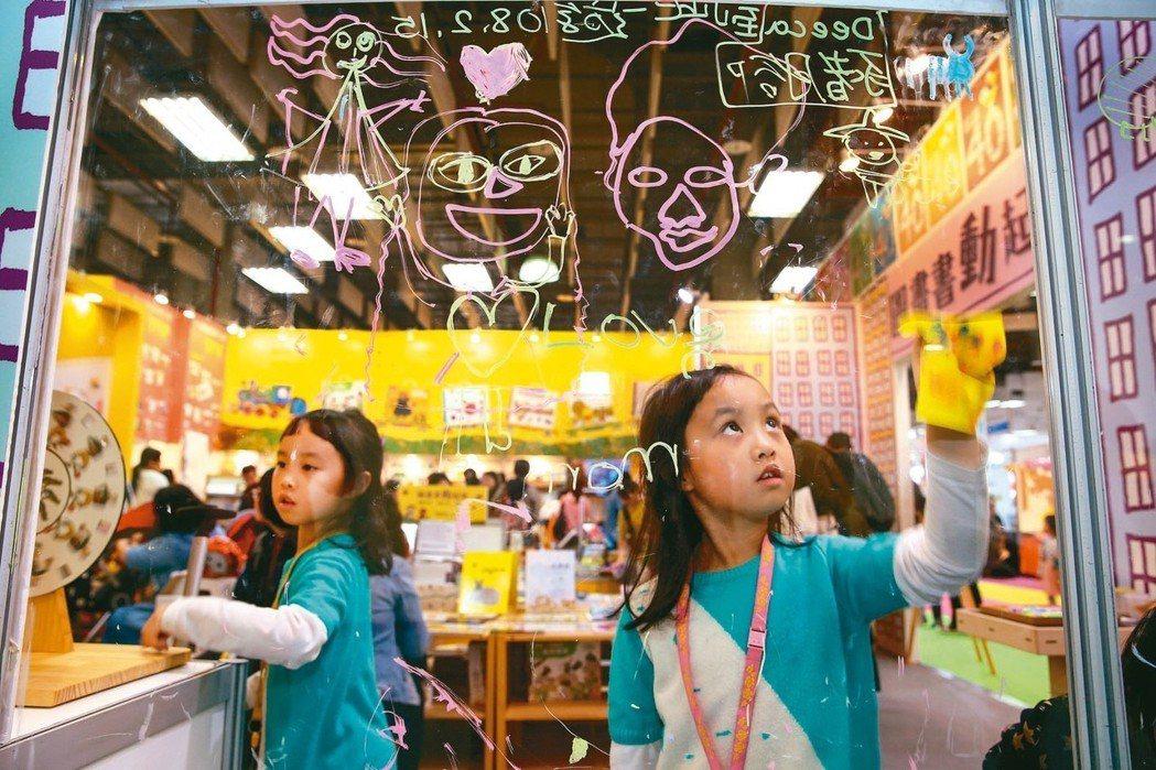 在國際書展上,小女孩將書中的圖像畫在玻璃上,鮮活了原本靜態的閱讀。聯合報願景工程...