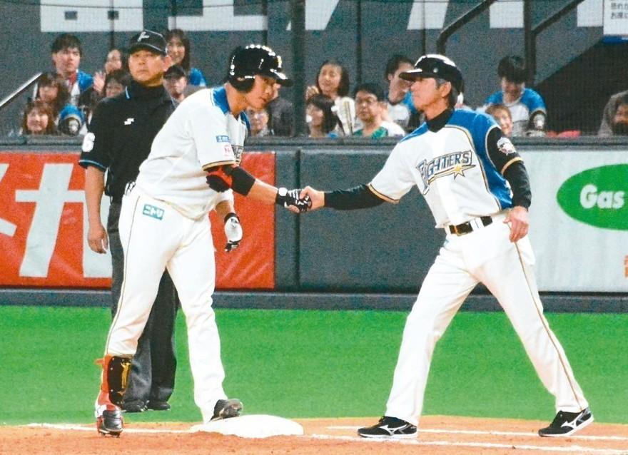 王柏融(左)敲出旅日首安,接受一壘跑壘指導員祝賀。 特派記者蘇志畬/攝影