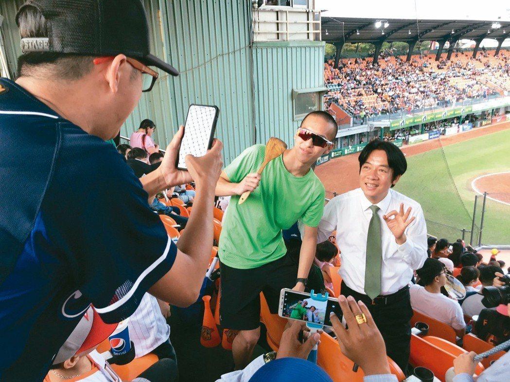 行政院前院長賴清德(右)昨到台南市立棒球場替統一獅加油,不少球迷排隊要他簽名合影...