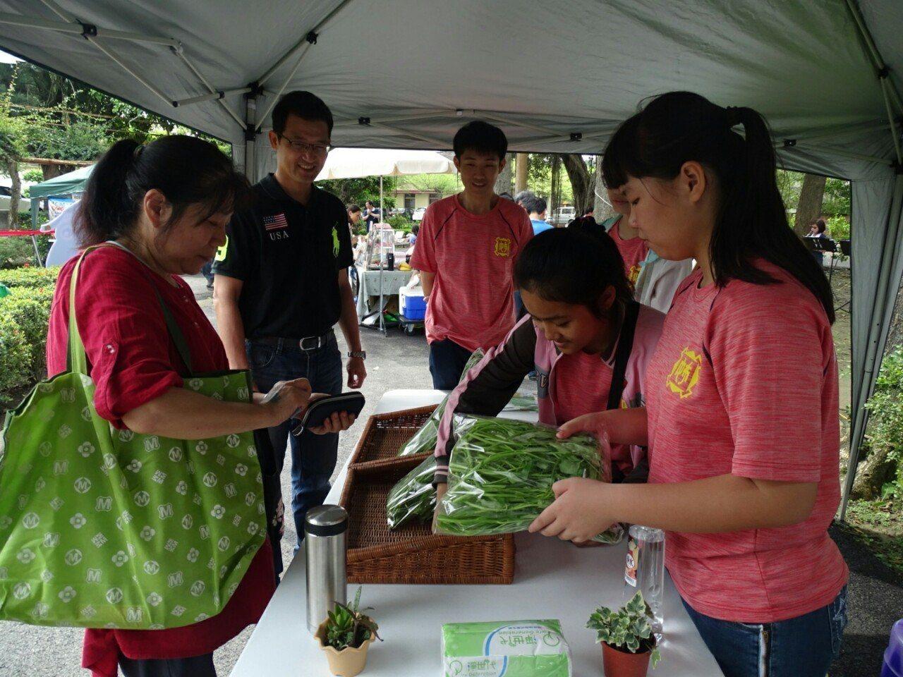 學生帶著自己種的空心菜到蒜頭糖廠的嘉減碳田園市集擺攤販售,很快賣光光。。記者謝恩...