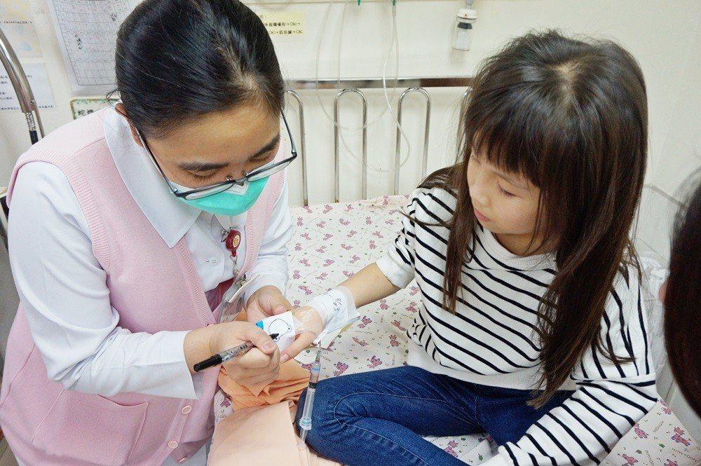 護理師在固定板上為病童畫上可愛塗鴉。圖/醫院提供
