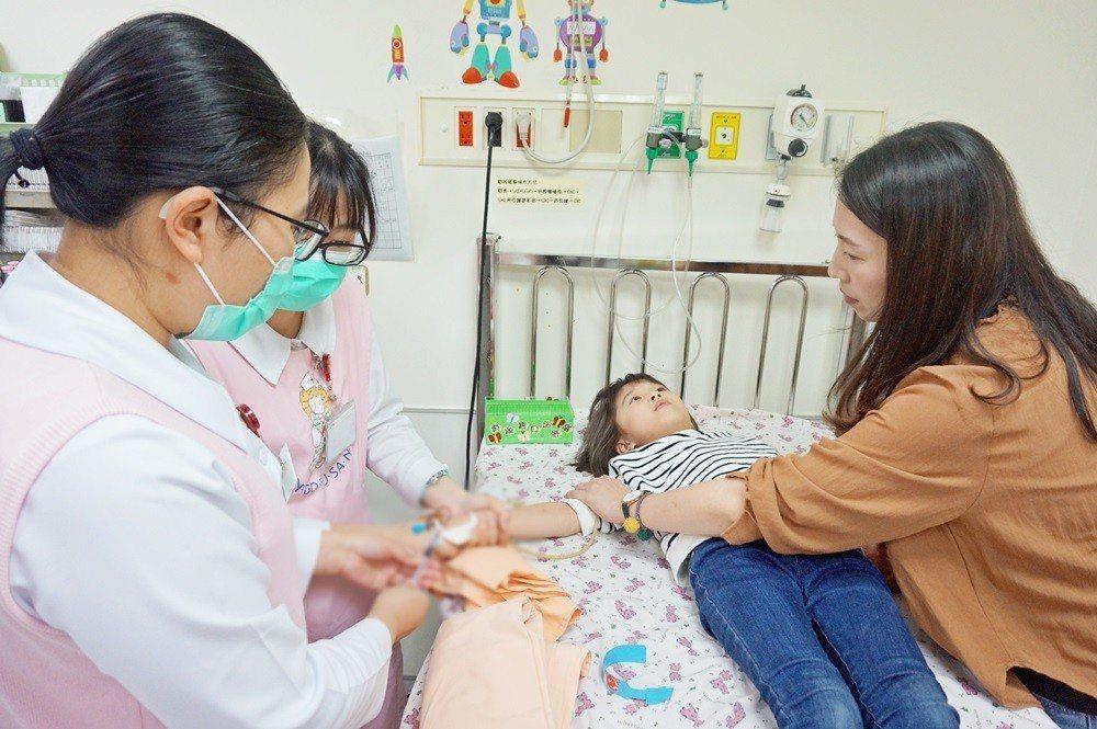 趁病童專心看電視,護理人員快速為病童進行治療。圖/醫院提供