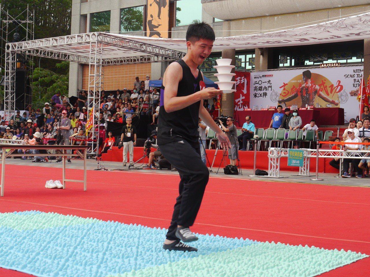 參賽者端碗盤行走比擬「天堂路」的尖銳地墊。 記者徐白櫻/攝影