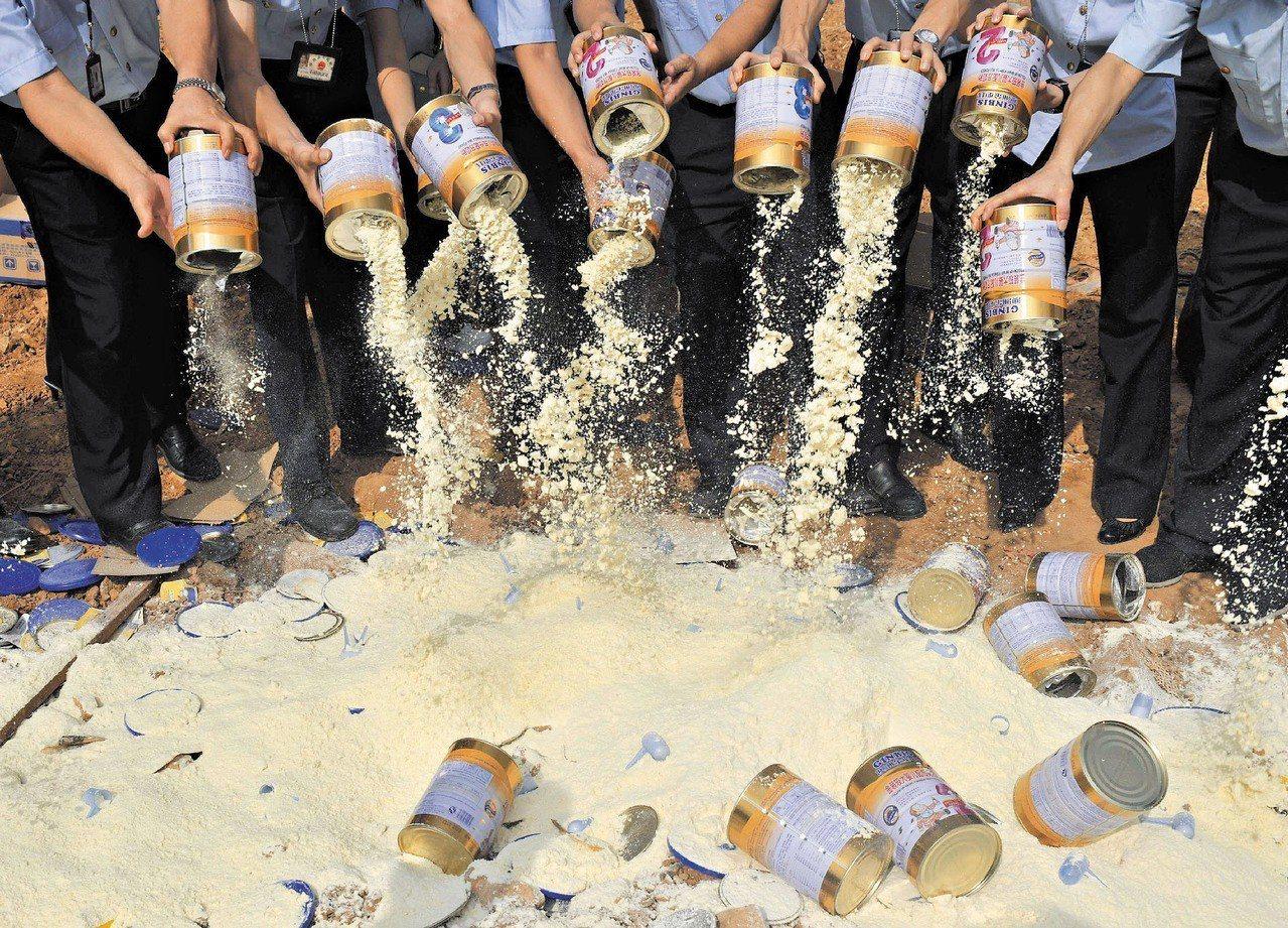 毒奶事件發生後,消費者上街頭抗議,並當場把毒奶粉倒掉。 (路透)