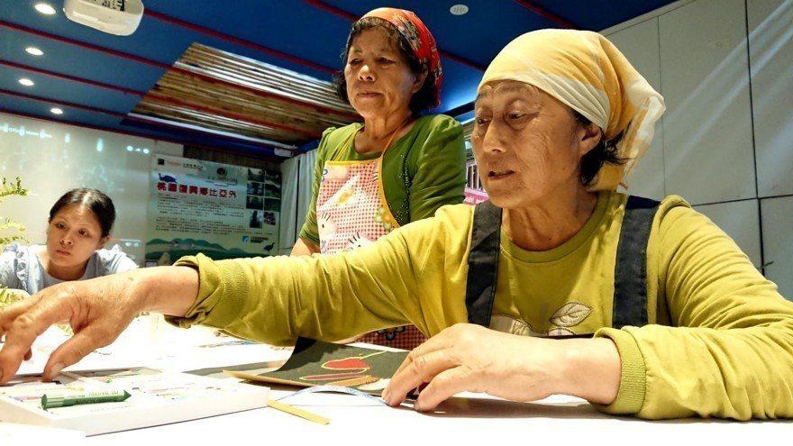 圖中戴著頭巾的是比亞外志工姐妹花,長者們興奮的拿著蠟筆畫出「呵護我的那雙手」。攝...