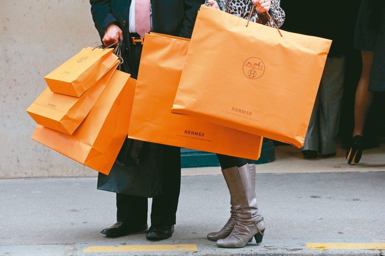 法國精品愛馬仕提供消費者亮橘色的提袋。 路透