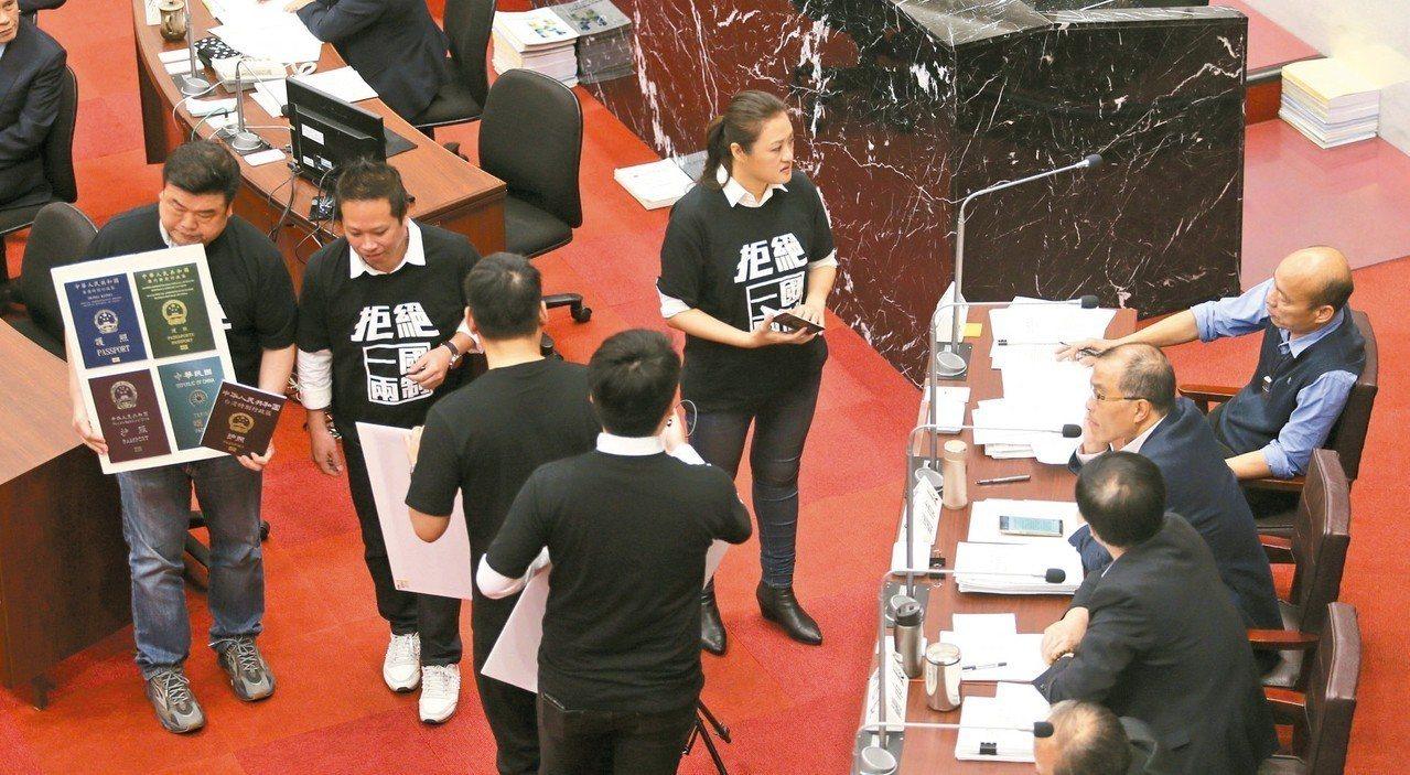 民進黨高雄市議員拿著港澳中護照要送給韓國瑜,質疑經貿團是「統戰團」。 記者劉學聖...