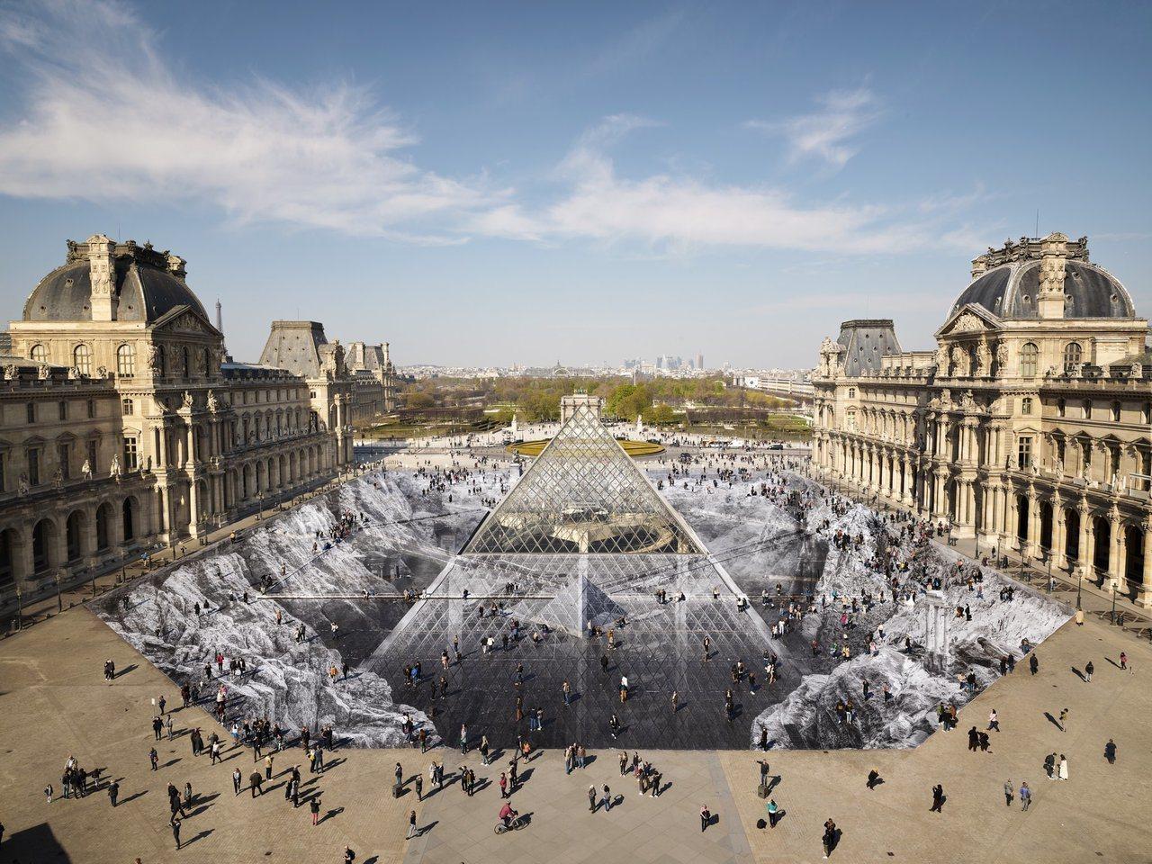 為慶祝羅浮宮金字塔落成30週年,藝術家JR鋪設了大型拼貼畫在金字塔前。圖片來源/...