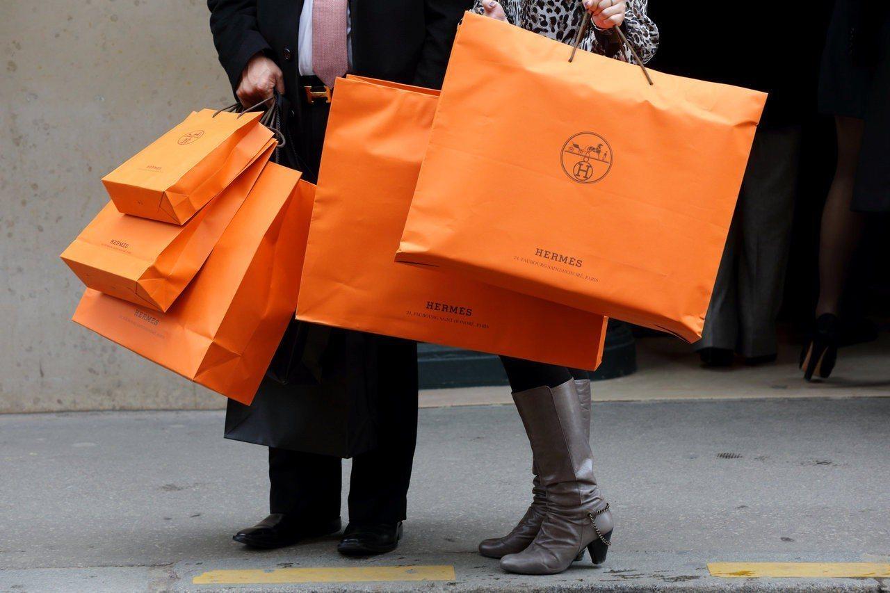 法國精品愛馬仕提供消費者亮橘色的提袋。路透