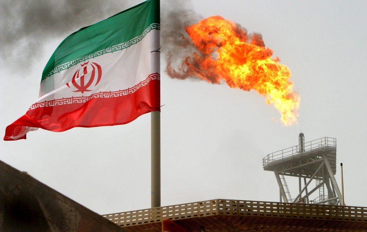 一面伊朗國旗在伊朗索羅什油田(Soroush)生產平台的火焰附近飄揚。路透