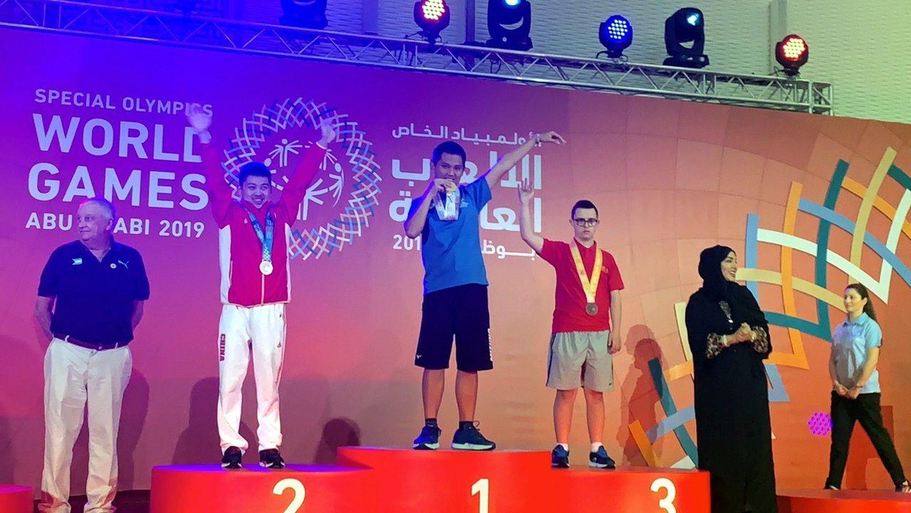 李東東(中)勇奪夏季特奧個人特奧滾球金牌,開心地咬金牌。圖/仁武特教學校提供