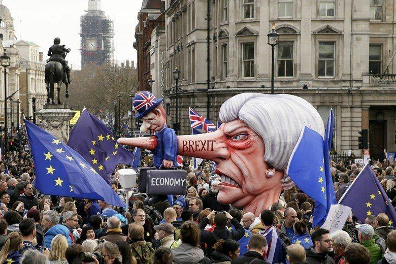 3月24日反脫歐人士集結遊行,其中遊行道具是英國首相梅伊的巨型頭像。 圖/美聯社