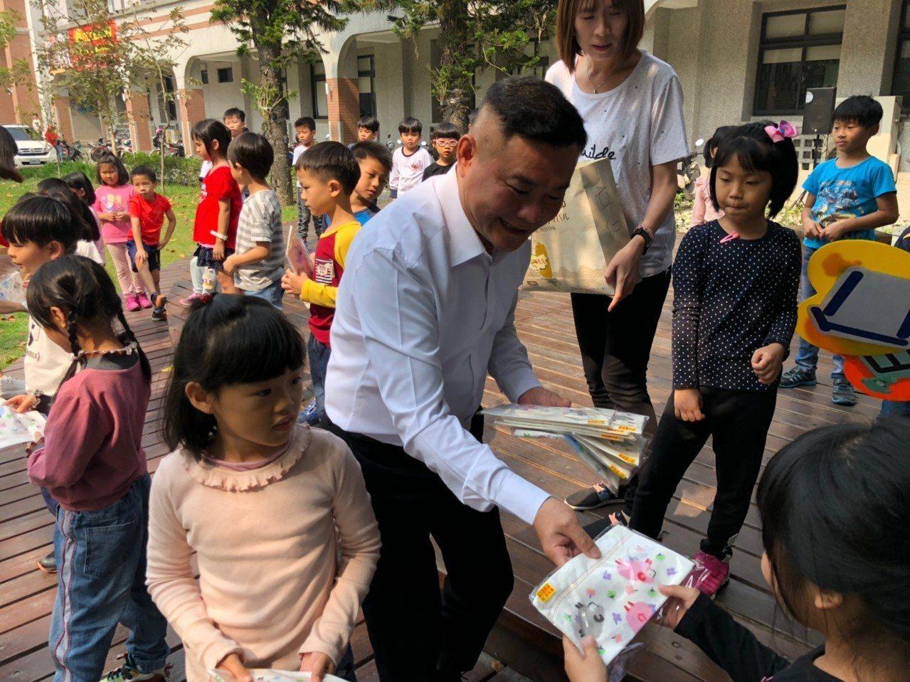 雲林虎尾鎮長丁學忠(中)一一發贈小方巾給學童。圖/虎尾鎮公所提供