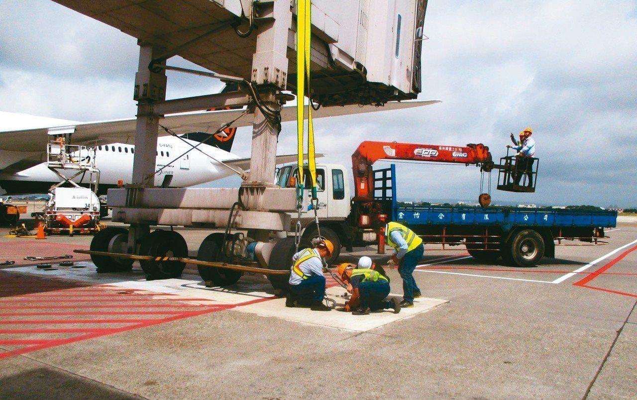 空橋操作人員將空橋固定於機坪防颱地錨上。 圖/桃機提供