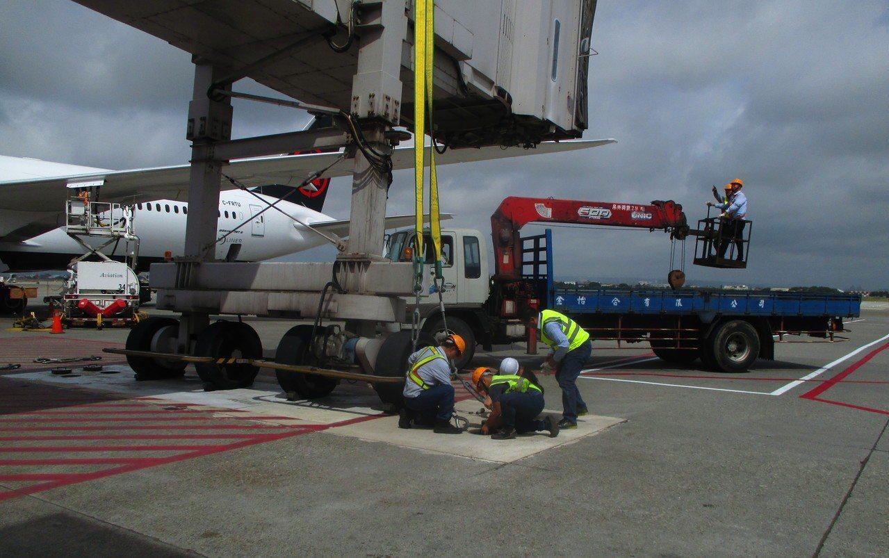 空橋操作人員將空橋固定於機坪防颱地錨上。圖/桃機提供