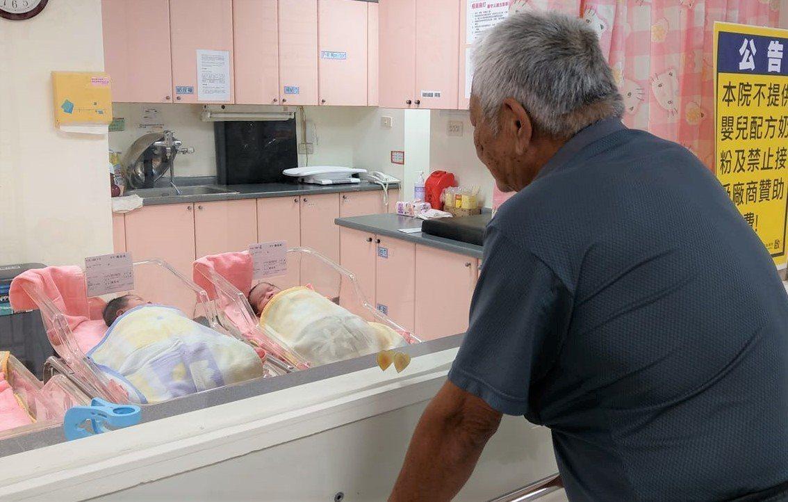 屏東恆春基督醫院昨天首度剖腹接生一對雙胞胎,院長陳志成拍下阿公在嬰兒室外凝視雙胞...