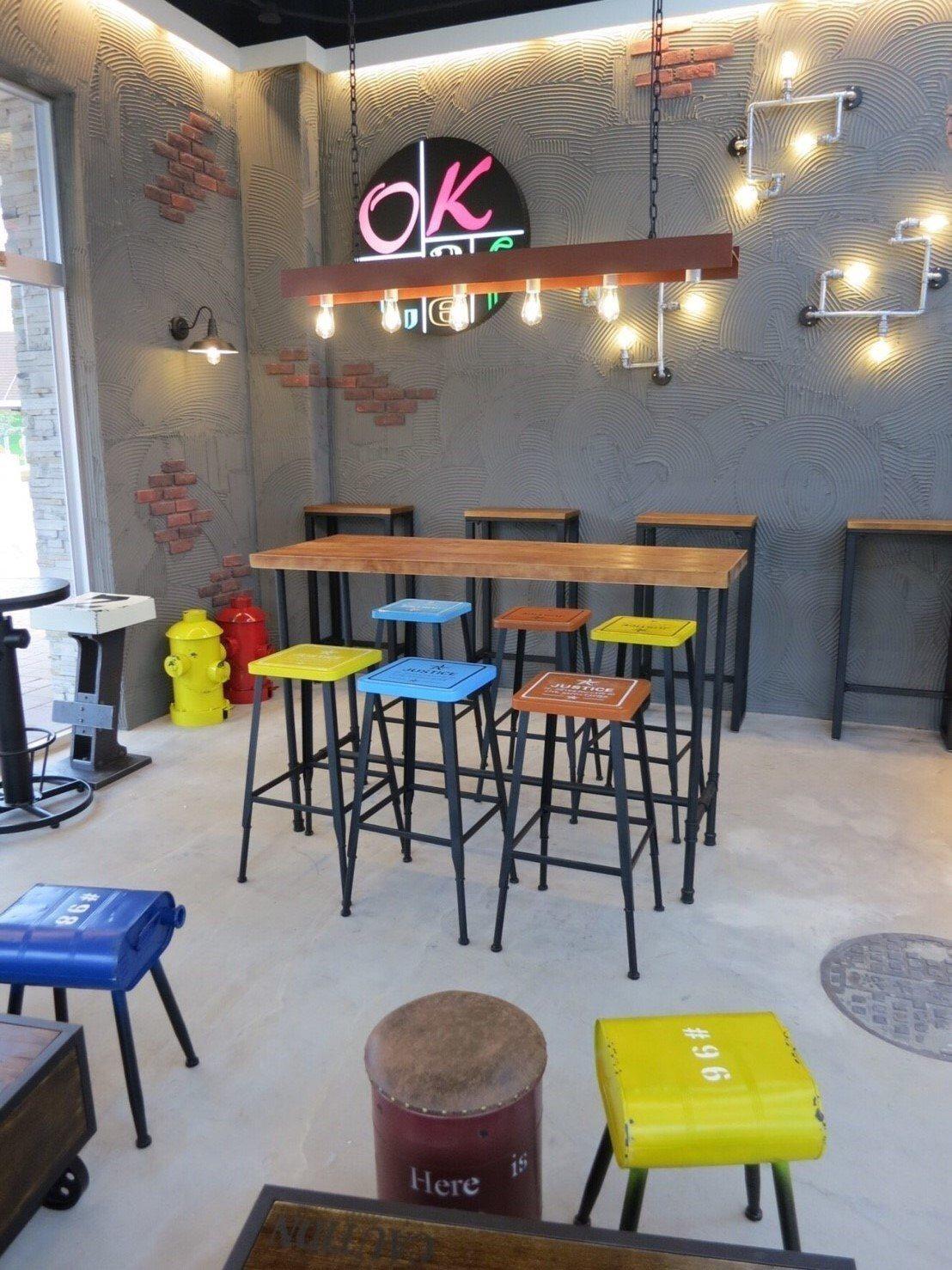 OKmart華泰中壢門市採用摩登工業風設計,運用鐵件、造型吊燈與彩色木紋椅詮釋餐...