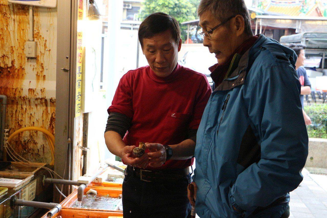 新北萬里龜吼漁民陳國賢(左)向顧客介紹各式海產。圖/農業局提供