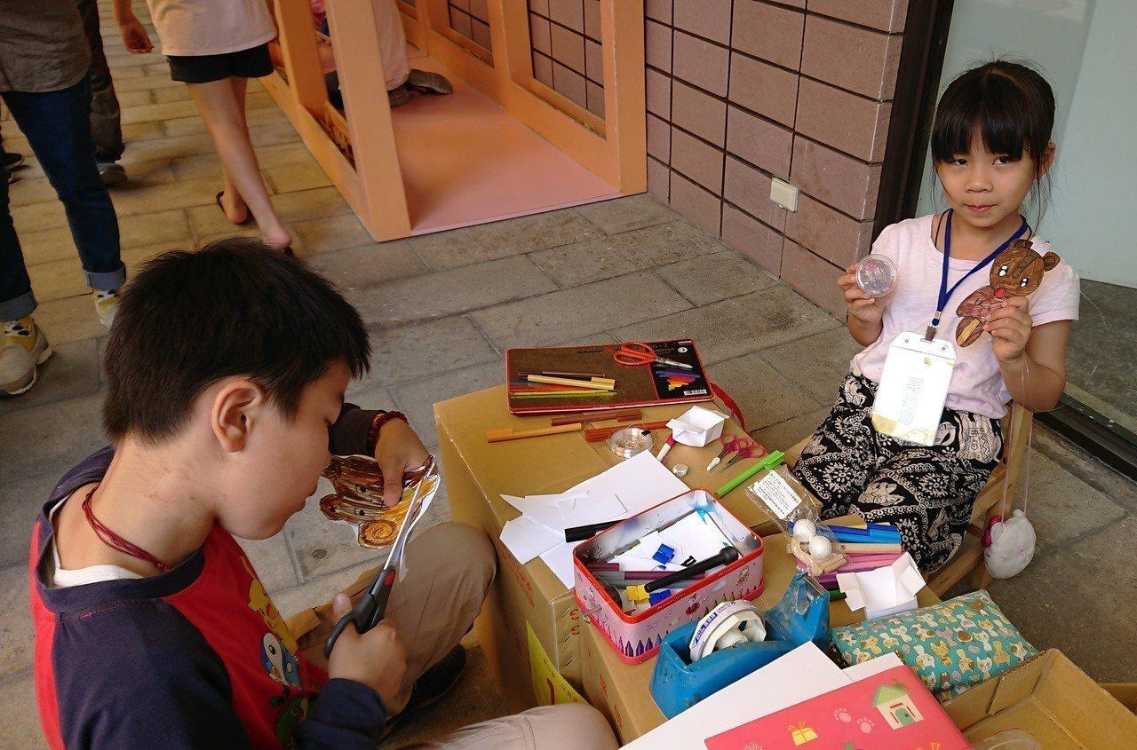 8歲的羅裕蓴自創熊造型「爬爬樂」玩具,不但擺攤教學賺零用錢,還能換其他玩具。記者...