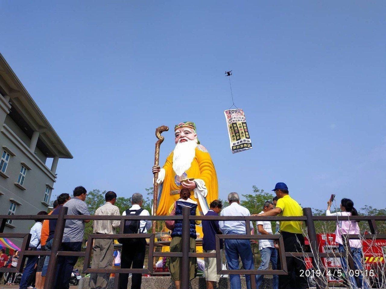 消防員利用無人機吊掛防火文宣到公墓上盤旋,宣傳效果佳。圖/ 玉井消防分隊提供