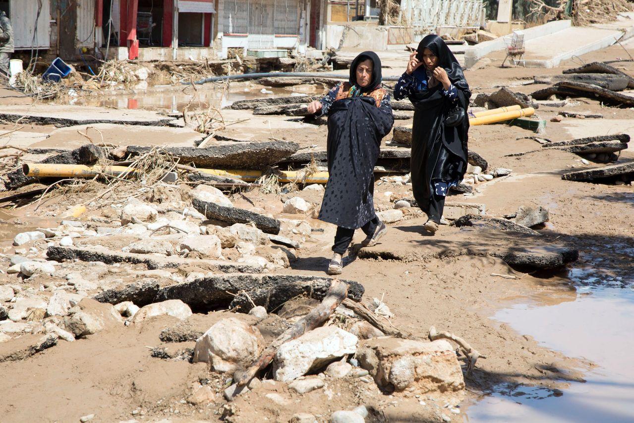 洪水退去後,伊朗西部洛雷斯坦省的兩名婦人走在滿布泥巴和殘骸的道路上。(法新社)