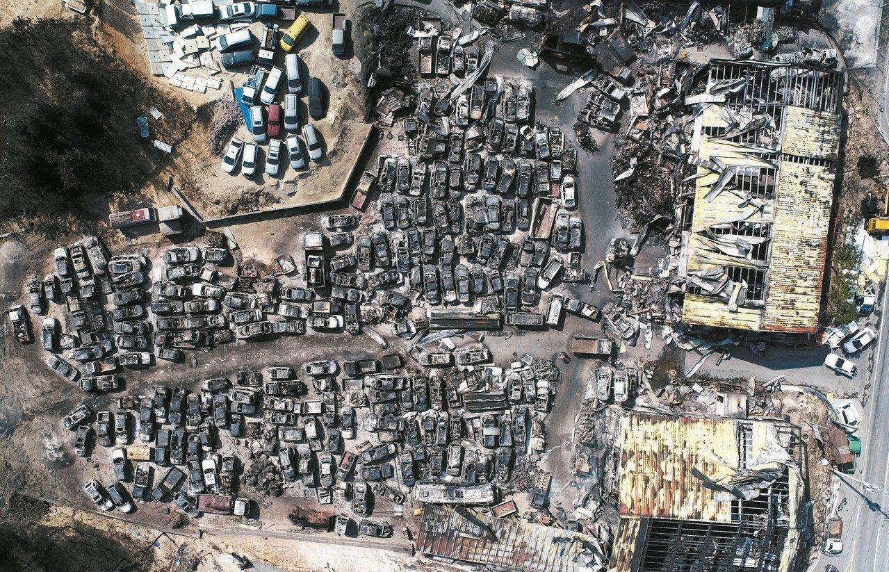 南韓四日晚間發生的森林大火造成慘重災情,空拍圖可見束草市一處堆滿遭燒毀車輛的回收...