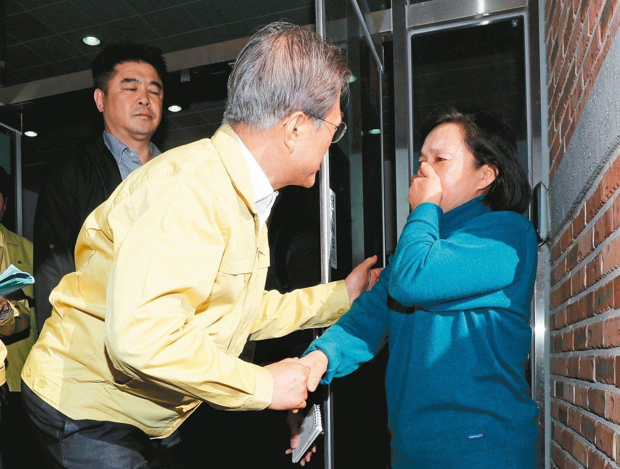 南韓總統文在寅(左)五日到江原道高城郡訪視因大火而被迫疏散的災民。 (美聯社)