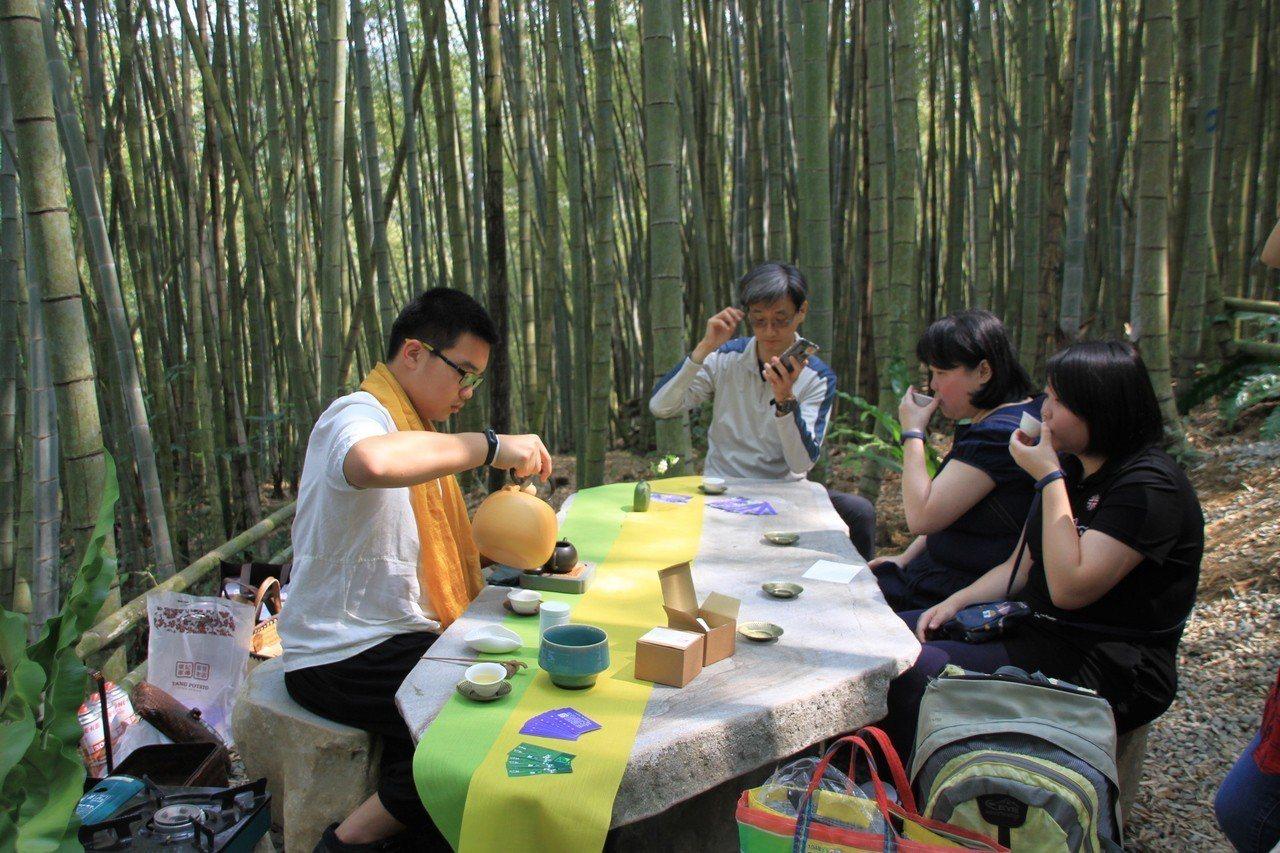 遊客在微風吹拂、竹林深處,坐在石桌茶席品賞高山茶香。記者卜敏正/攝影