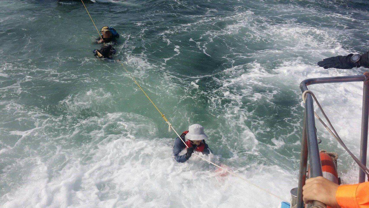 海巡人員拋繩索讓救生艇落海的2人拉繩獲救。記者林保光/翻攝