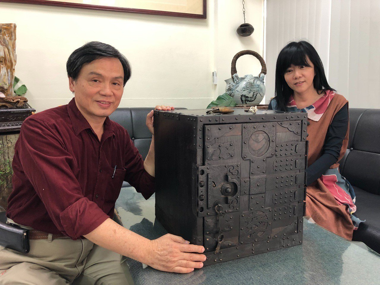 李淑娟(右)收藏木製保險箱,梁志忠(左)鑑定應是日本江戶後期產品,以木板蒙上鐵皮...