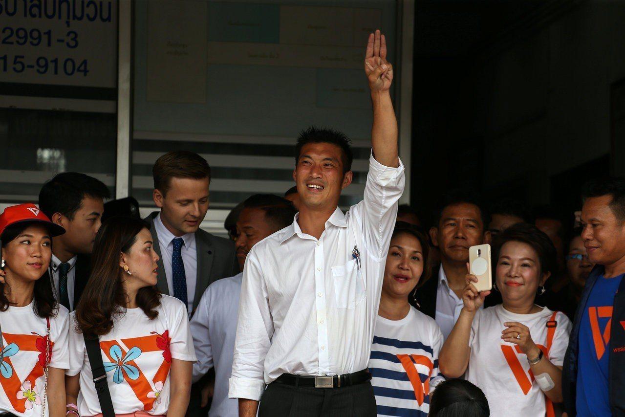 泰國未來前進黨黨魁塔納通(中)6日應訊後,走出警局時比出電影「飢餓遊戲」中象徵反...
