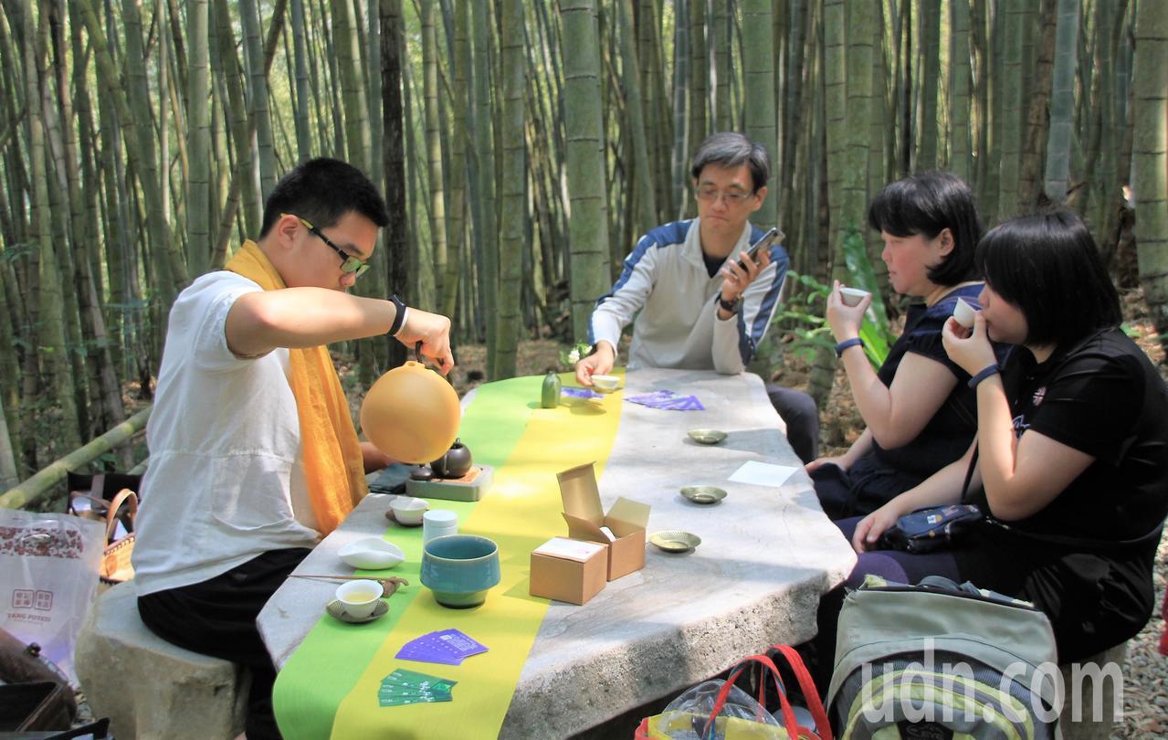 遊客坐在竹林深處石桌茶席,品賞高山茶香。記者卜敏正/攝影
