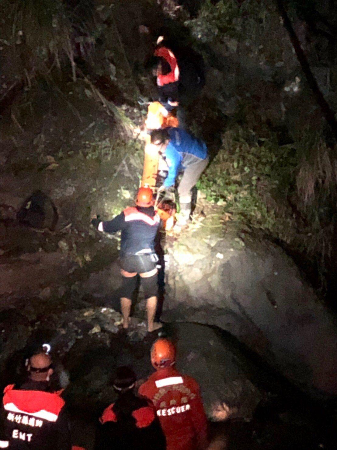 消防人員不敢大意,利用微弱燈光,垂降至20公尺下的懸崖將人員救出。圖/竹縣消防局...