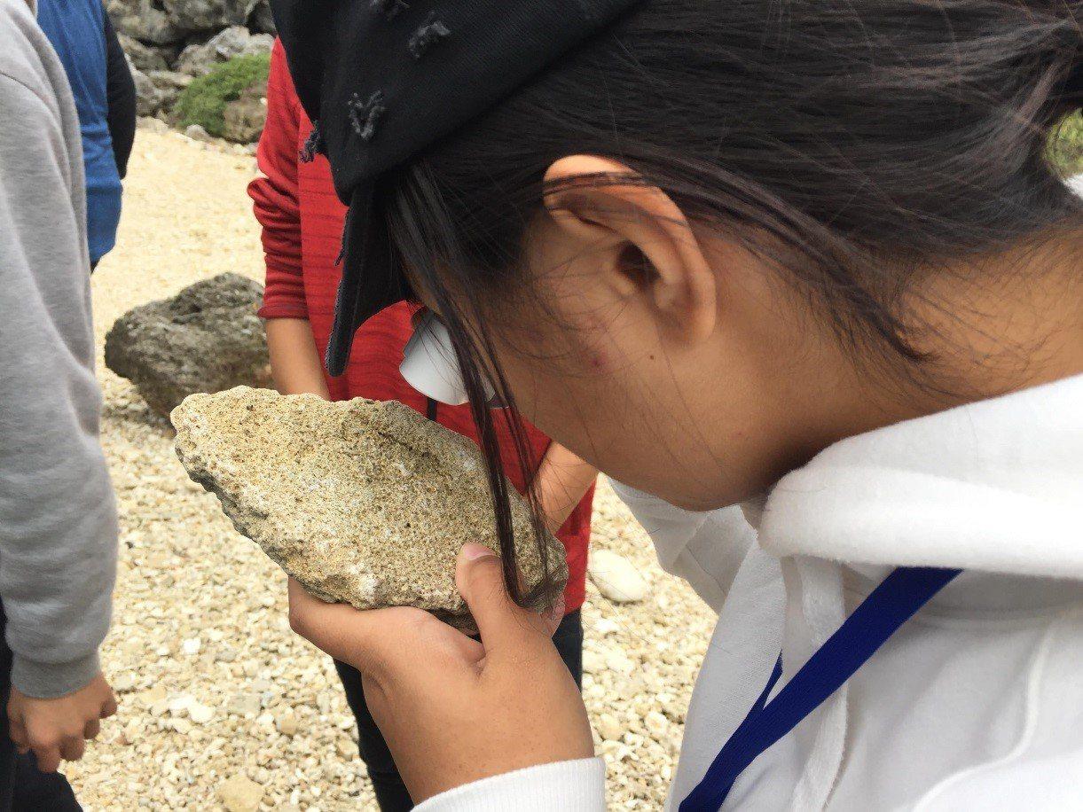 學生在野外使用放大鏡觀察標本上的微體化石。圖/教育部提供