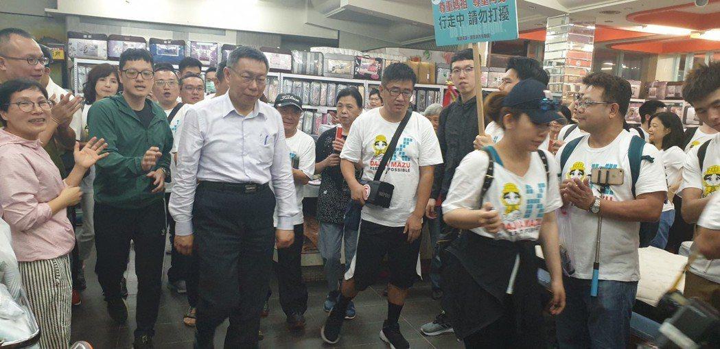 台北市長柯文哲跟著大甲媽遶境,隨行人員帶著扛棒,寫著「尊重媽祖,尊重阿北,行走中...