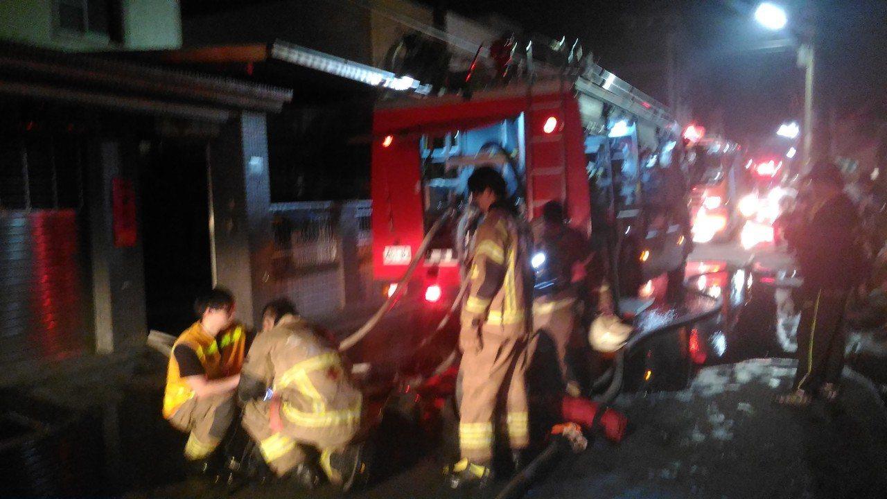 台南市安南區環福街民宅汽車倉庫火災,消防人員出水滅火。記者黃宣翰/攝影