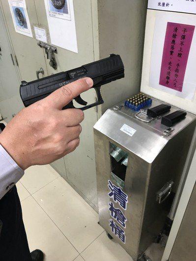 台中市警員示範正確清槍動作,食指應與槍身平行擺放,切忌放入護弓內。 記者林佩均/...